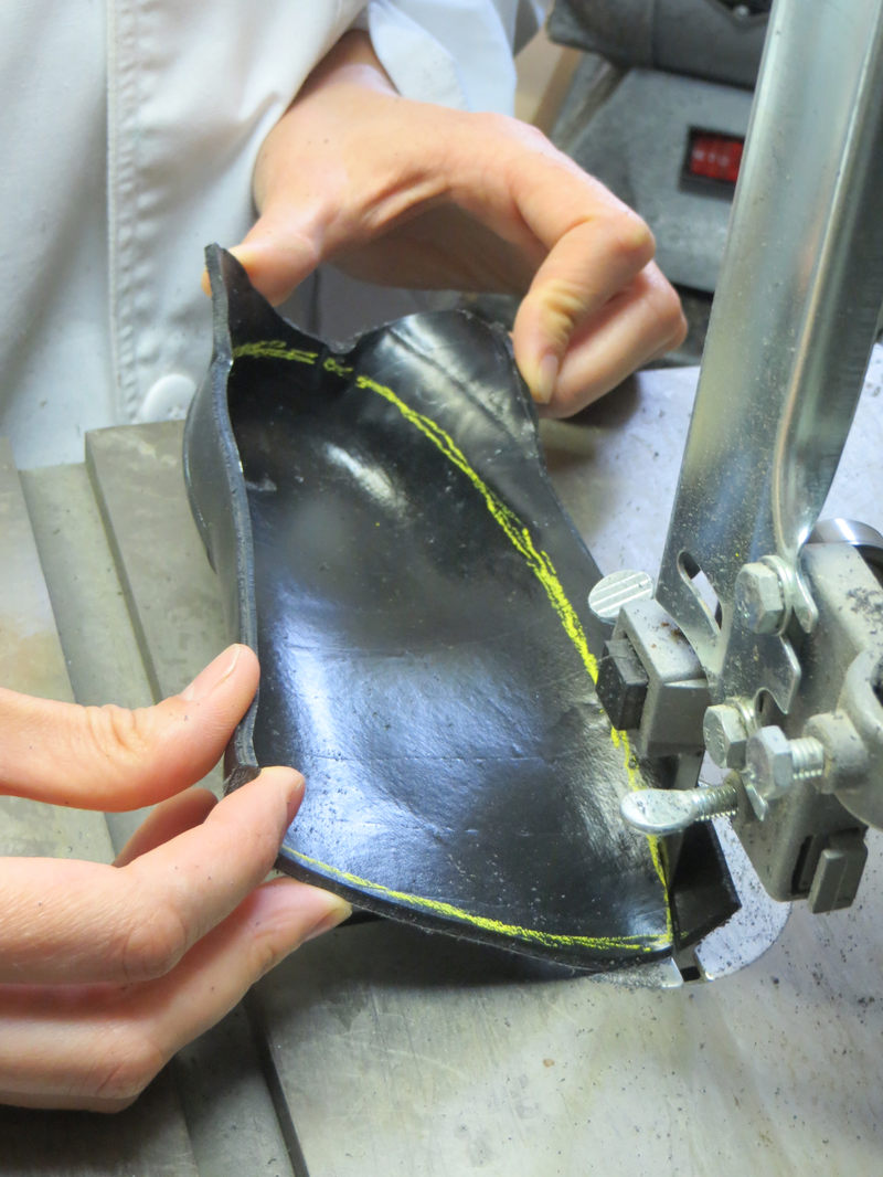 Excess material is cut from the orthotic shell using a bandsaw. (Custom orthotics fabrication process, step 10.)