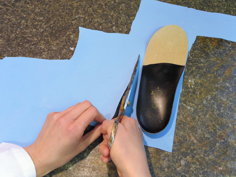 Blue cushiony material (poron) is cut out. (Custom orthotics fabrication process, step 14.)